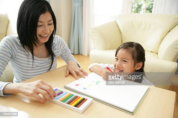 Mid adult woman drawing with her daughter
