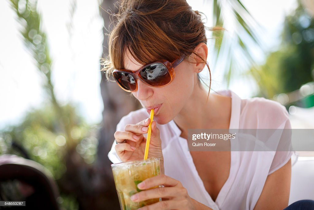 Mid adult woman drinking orange juice at pavement cafe, Castelldefels, Catalonia, Spain