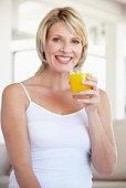 Mid Adult Woman Drinking Orange Juice