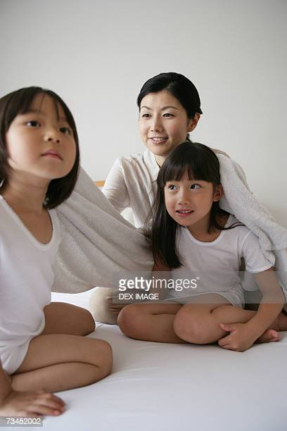 Mid adult woman drying her daughter's hair on the bed and smiling