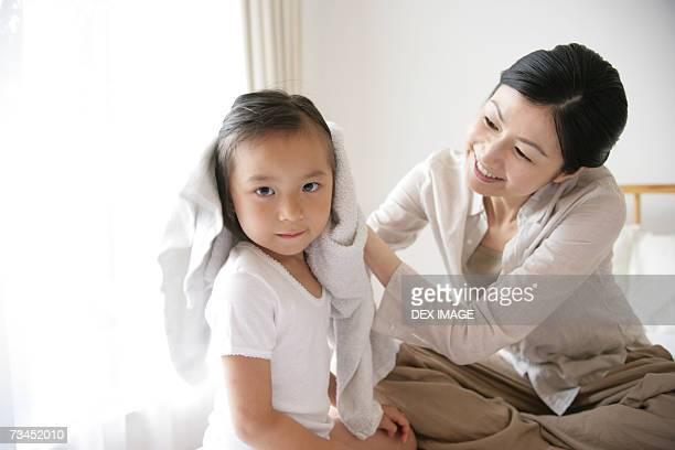 Mid adult woman drying her daughter's hair on the bed
