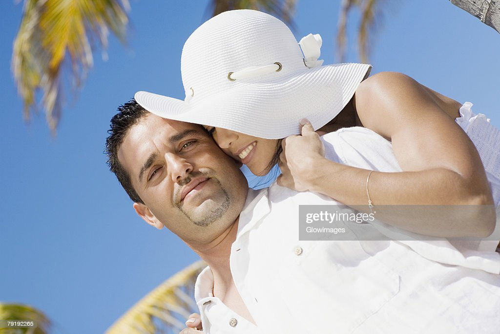 Mid adult woman embracing a mid adult man from behind and smiling : Foto de stock