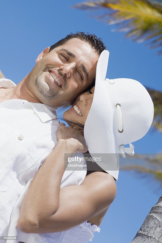 Mid adult woman embracing a mid adult man from behind : Stock Photo