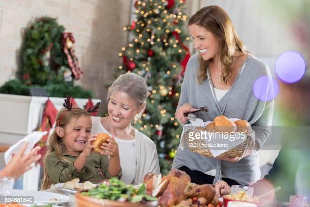 Half volwassen vrouw geniet brood serveren tijdens het kerstdiner