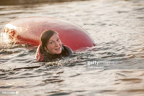 Mid adult woman falling in water with kayak