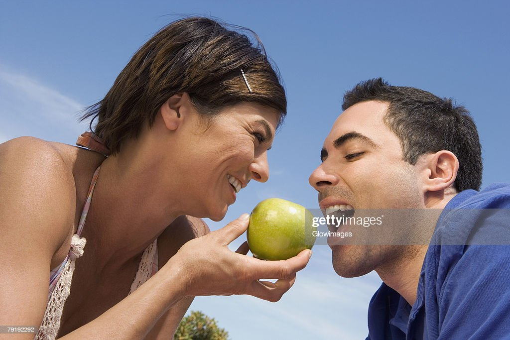 Mid adult woman feeding a green apple to a mid adult man : Stock Photo