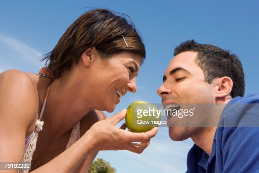 Mid adult woman feeding a green apple to a mid adult man : Foto de stock
