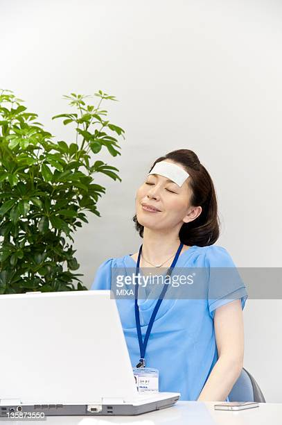 Mid adult woman feeling good by cooling gel sheet on forehead