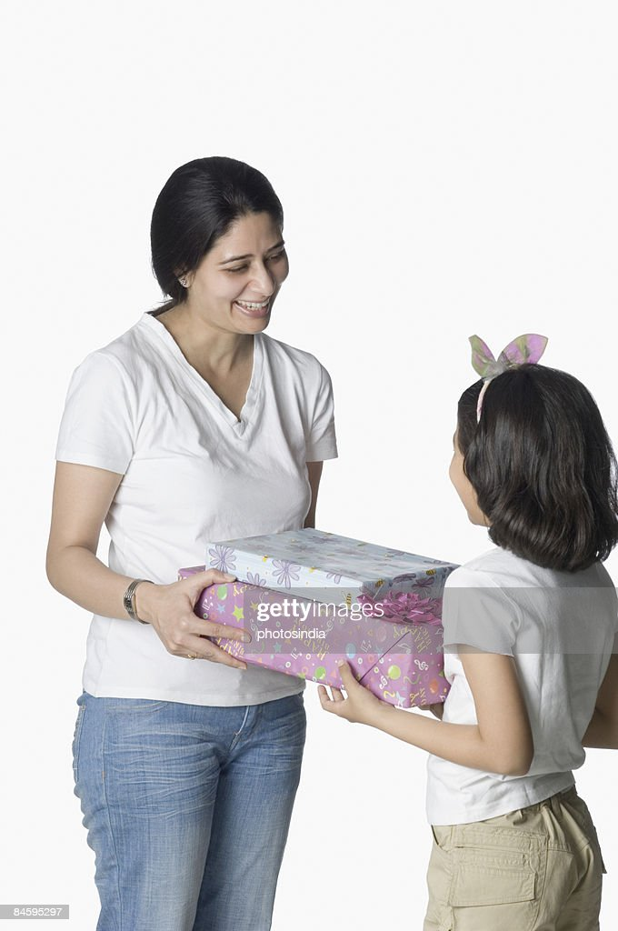 Mid adult woman giving gifts to her daughter