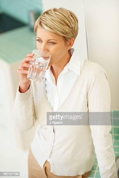 Frau mittleren Alters, ein Glas Wasser
