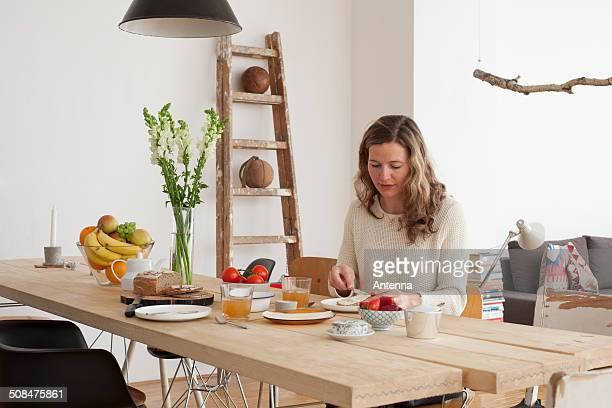 Mid adult woman having breakfast at table