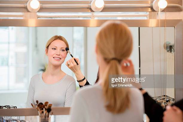 Mid adult woman having make-up applied
