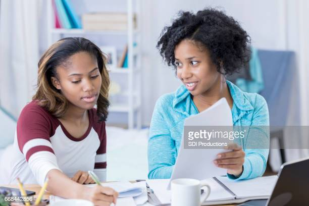 Mid adult woman helps young college student with homework