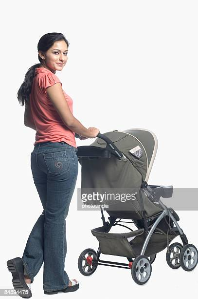 Mid adult woman holding a baby stroller