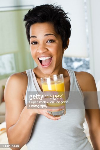Mid adult woman holding a glass of orange juice : Stock Photo