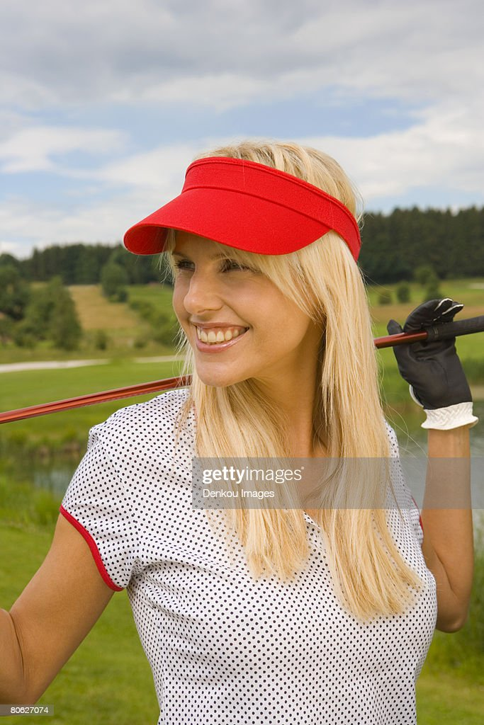 Mid adult woman holding a golf club and smiling : Stock Photo