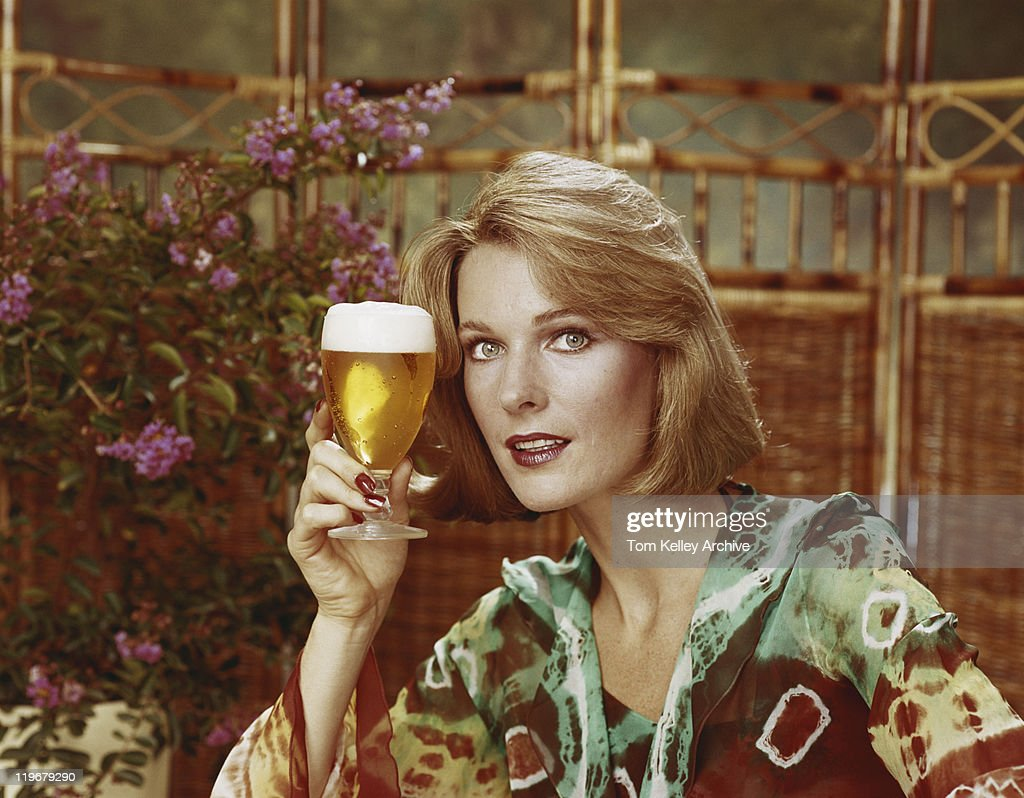Mid adult woman holding beer glass, portrait, close-up : Stock Photo