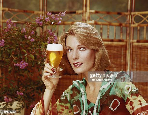 Mid adult woman holding beer glass, portrait, close-up