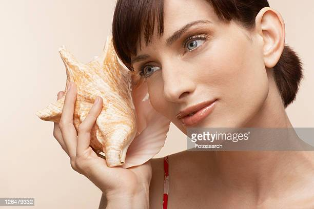Mid adult woman holding conch shell to ear