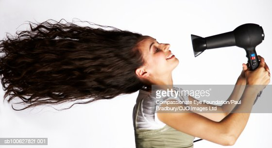 Mid adult woman holding hair dryer in front of face, side view : Stock Photo