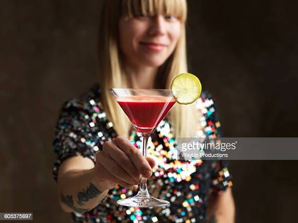 Mid adult woman holding raw juice in cocktail glass garnished with lime slice looking at camera smiling