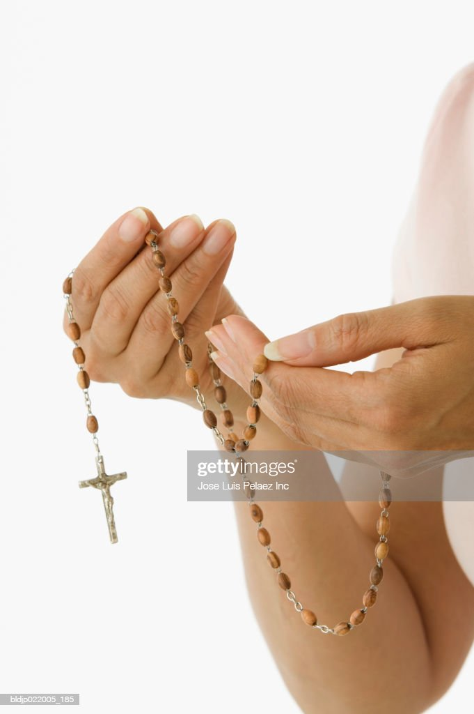 Mid adult woman holding rosary beads and crucifix