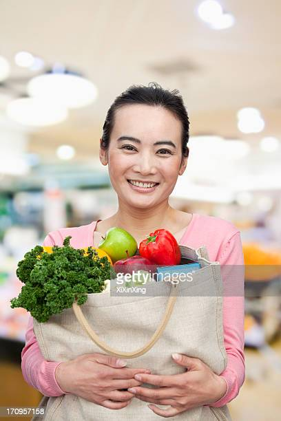 Mid Adult Woman Holding Shopping Bag with Fruits and Vegetables