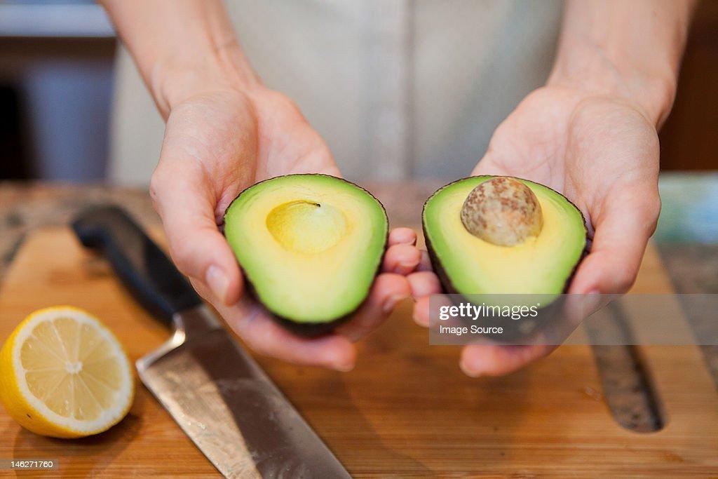 Mid adult woman holding sliced avocado