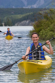 Mid adult woman in kayak, smiling, man in background
