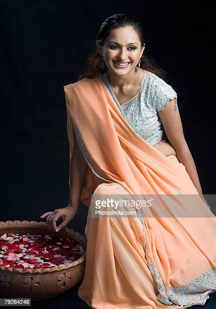 Mid adult woman in lehenga choli and sitting on a stool with a bowl of petals