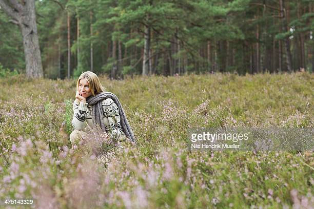 Mid adult woman in meadow with hand on chin