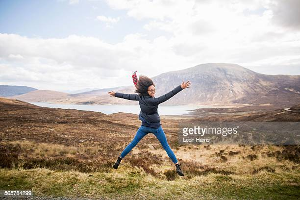 Mid adult woman in mountains doing star jump, Isle of Skye, Hebrides, Scotland