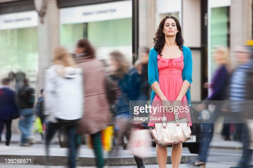 Mid adult woman in pink dress standing still in crowded city