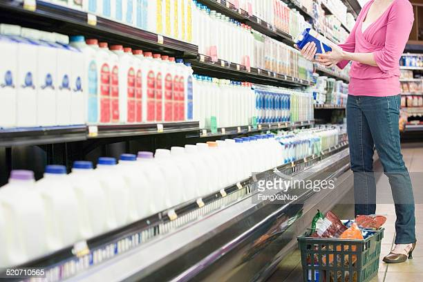 Mid adult woman in supermarket holding milk