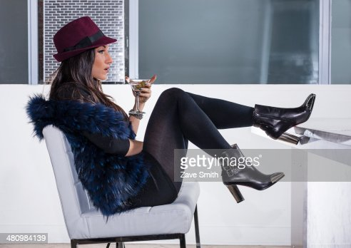 Mid adult woman in with feet up in cocktail bar : Stock Photo