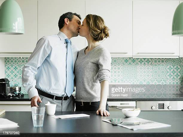 Mid adult woman kissing businessman in kitchen