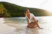 Mid adult woman kneeling on sandy beach, St. John, US Virgin Islands, USA