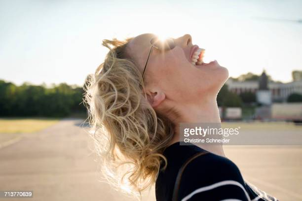 Mid adult woman laughing with head back in sunlight