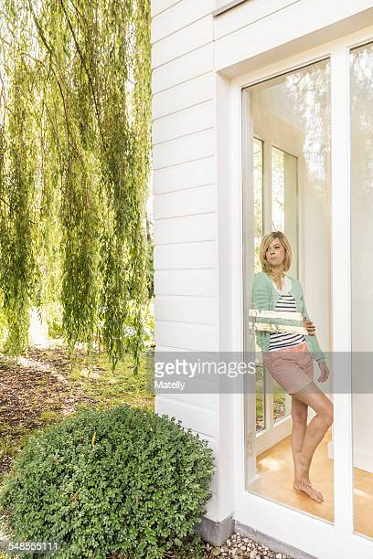 Mid adult woman leaning against and looking through house window