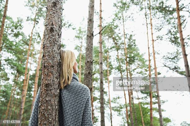 Mid adult woman leaning against tree, low angle