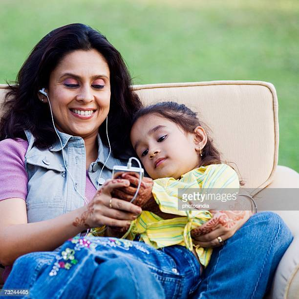 Mid adult woman listening to an MP3 player with her daughter lying on her lap
