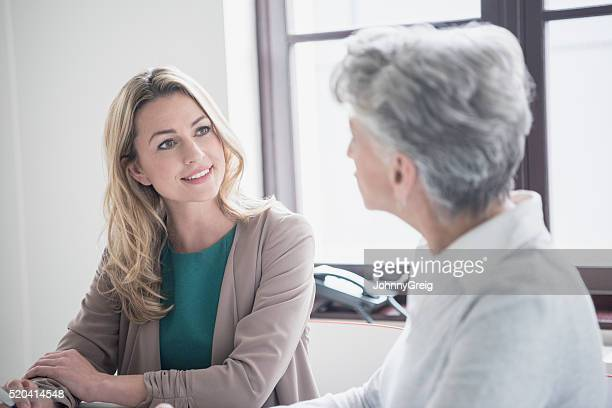 Mid adult woman listening to mature female colleague in meeting
