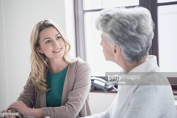 Mitte Erwachsene Frau hören Reife weibliche Kollegen in den Meetingräumen
