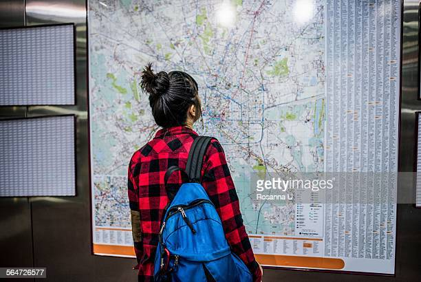 Mid adult woman looking at street map, Milan, Italy