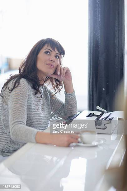 Mid adult woman looking up with typewriter