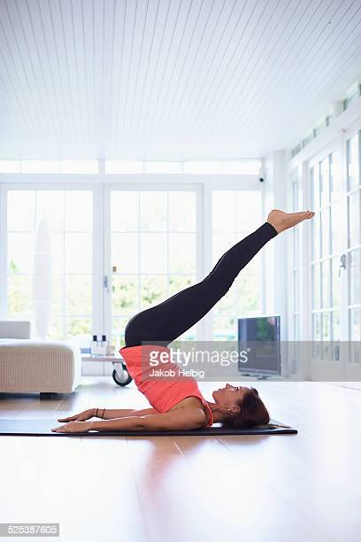 Mid adult woman lying on back practicing yoga in living room