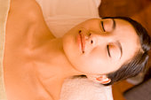 Mid adult woman lying on bed in beauty salon, closing eyes
