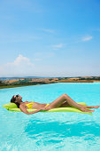 Mid adult woman lying on inflatable mattress in swimming pool