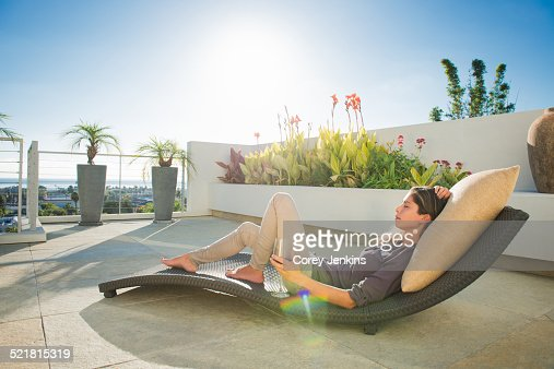 Mid adult woman lying on lounger in penthouse rooftop garden, La Jolla, California, USA