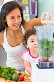 Mid adult woman making smoothie for toddler niece in kitchen